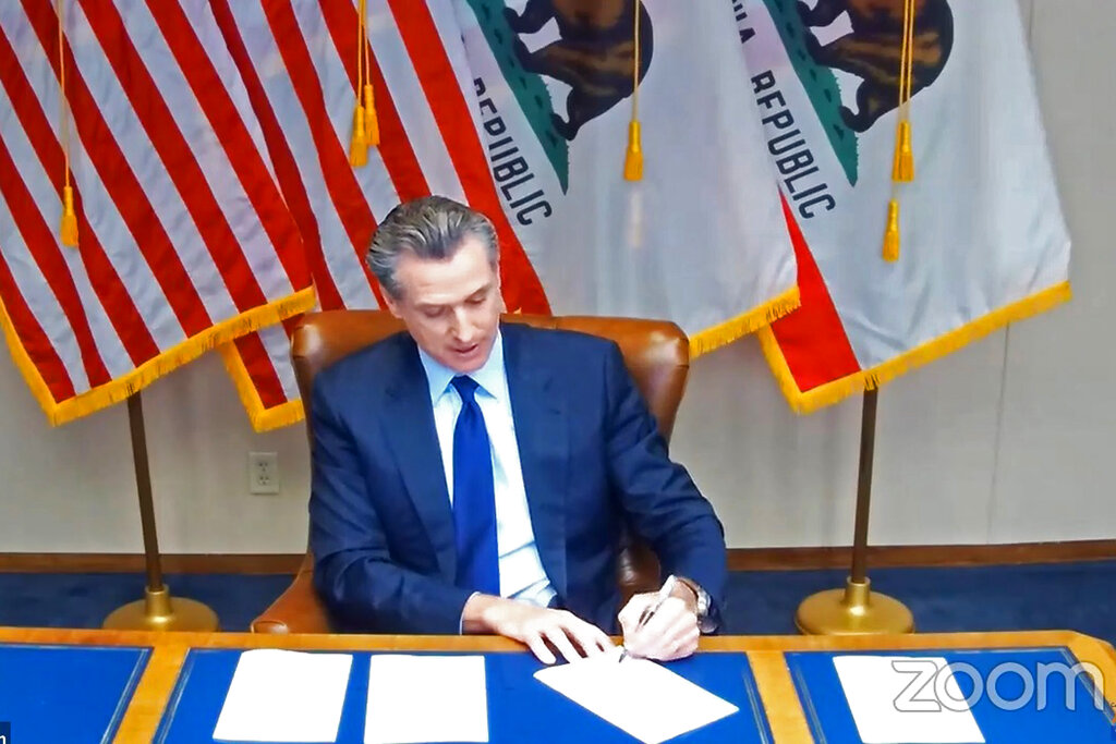 "In this image taken during a video broadcast via Zoom, California Gov. Gavin Newsom signs a law on Sept. 25, 2020, in Sacramento that for the first time defines ""medical necessity,"" a move aimed at requiring private health insurance plans to pay for more mental health and drug addiction treatments. (Zoom via AP)"
