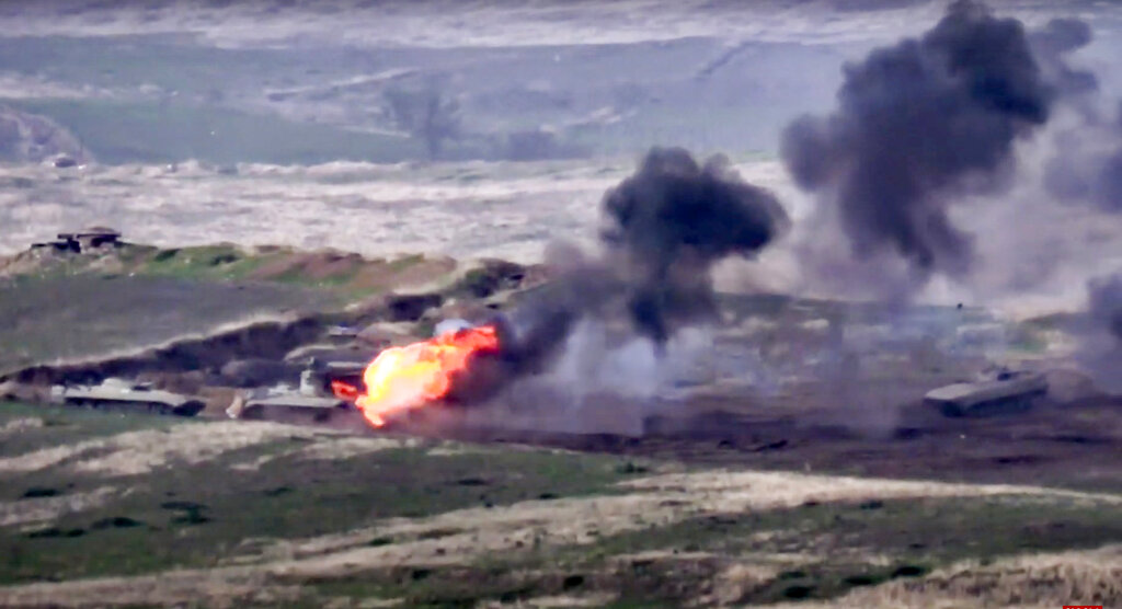 In this image taken from a footage released by Armenian Defense Ministry on Sept. 27, 2020, Armenian forces destroy Azerbaijani military vehicle at the contact line of the self-proclaimed Republic of Nagorno-Karabakh, Azerbaijan. (Armenian Defense Ministry via AP)