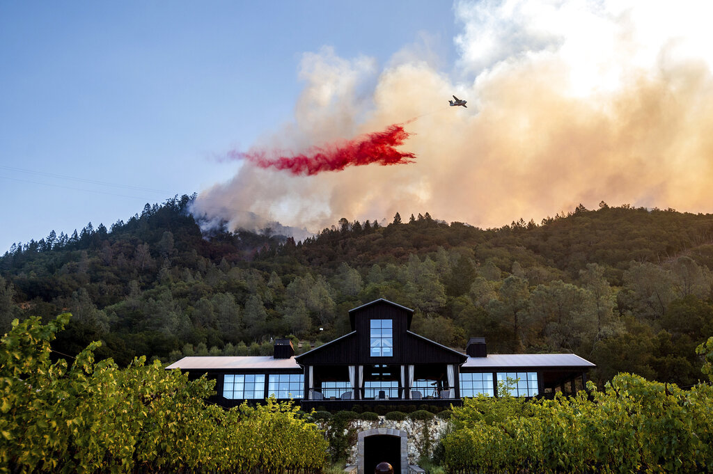 An air tanker drops retardant on the Glass Fire burning above Davis Estates winery in Calistoga, Calif., on Sept. 27, 2020. (AP Photo/Noah Berger)