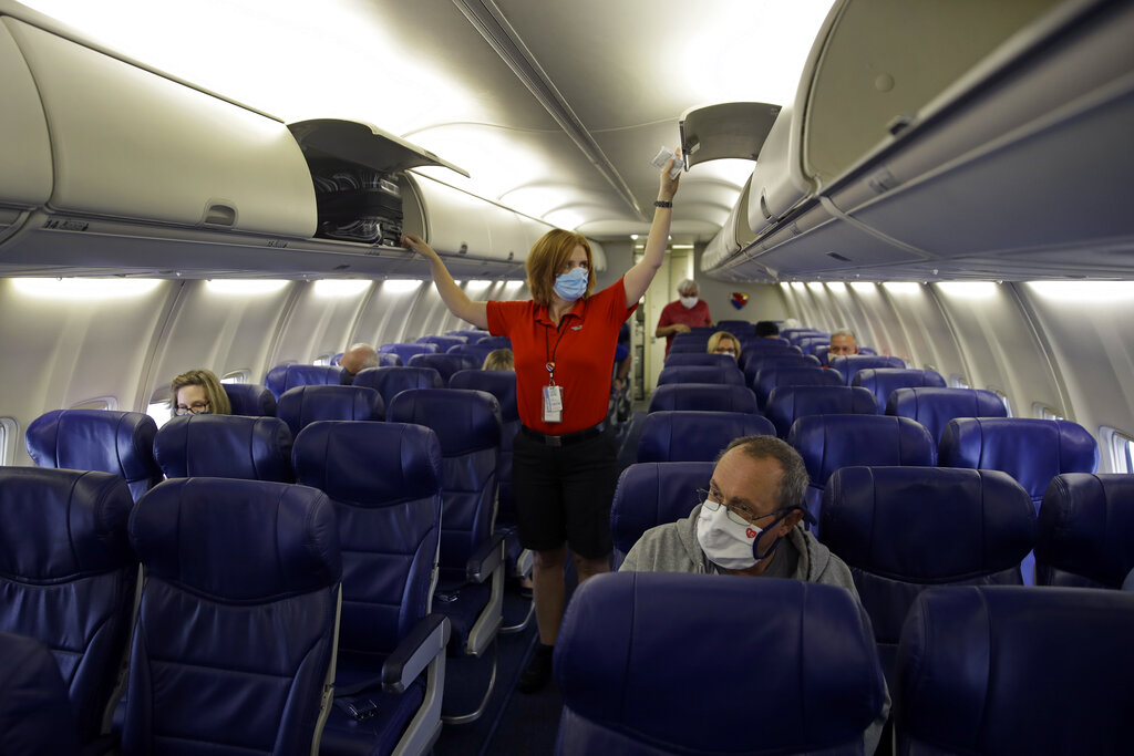 In this May 24, 2020, file photo, a Southwest Airlines flight attendant prepares a plane bound for Orlando, Fla. for takeoff at Kansas City International airport in Kansas City, Mo. (AP Photo/Charlie Riedel, File)