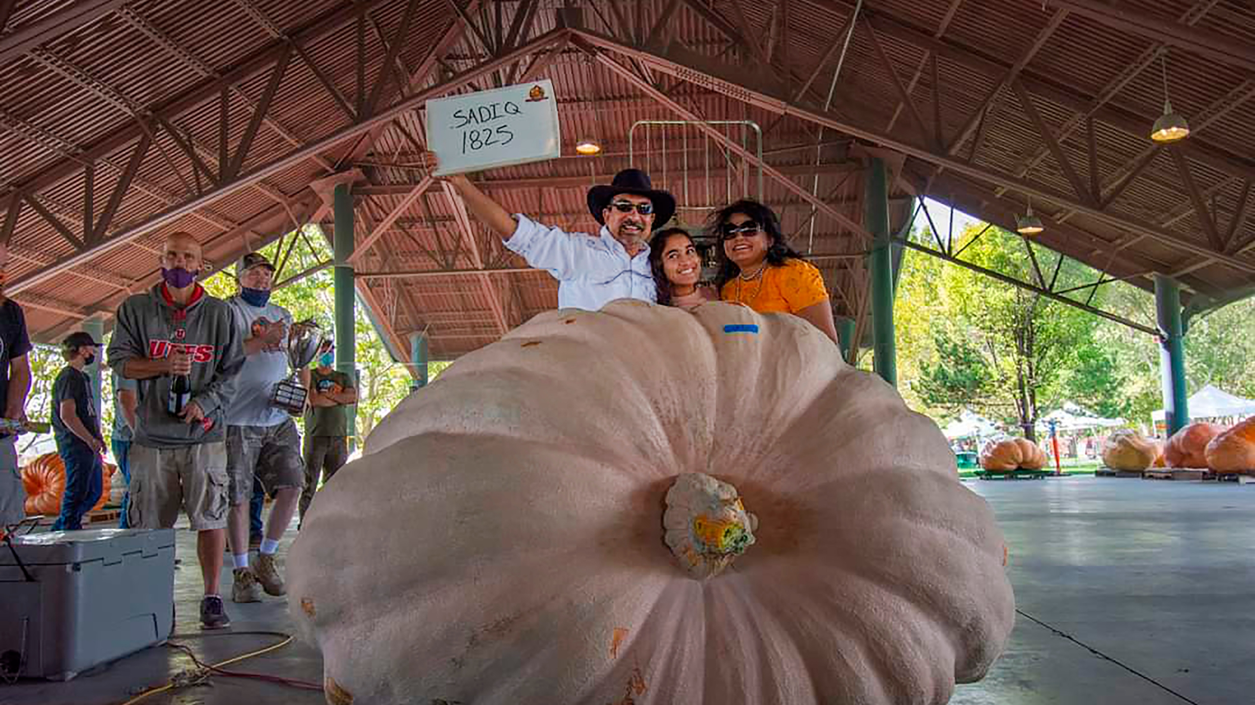 This photo provided by Jim Seamons shows Mohamed Sadiq posing for a photo with his family and his 1,825 pounds (828 kilograms) pumpkin at the 16th Annual UGPG Thanksgiving Point Weigh-Off winning First Place and named the largest pumpkin grown in Utah outside of a greenhouse on Saturday, Sept. 26, 2020 in Lehi, Utah. The Utah Giant Pumpkin Growers has recorded eight pumpkins in Utah this year weighing over 1,000 pounds (454 kilograms), setting a state record. (Ryann Seamons via AP)