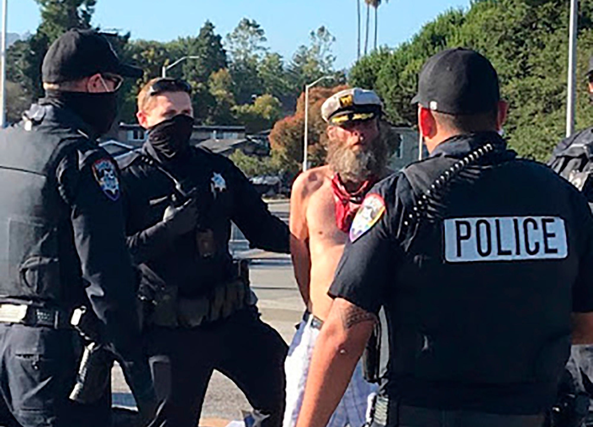 This July 5, 2020, photo provided by the Santa Cruz Police Department shows Ole Hougen being taken into custody by police officers in Santa Cruz, Calif. (Santa Cruz Police Department via AP)