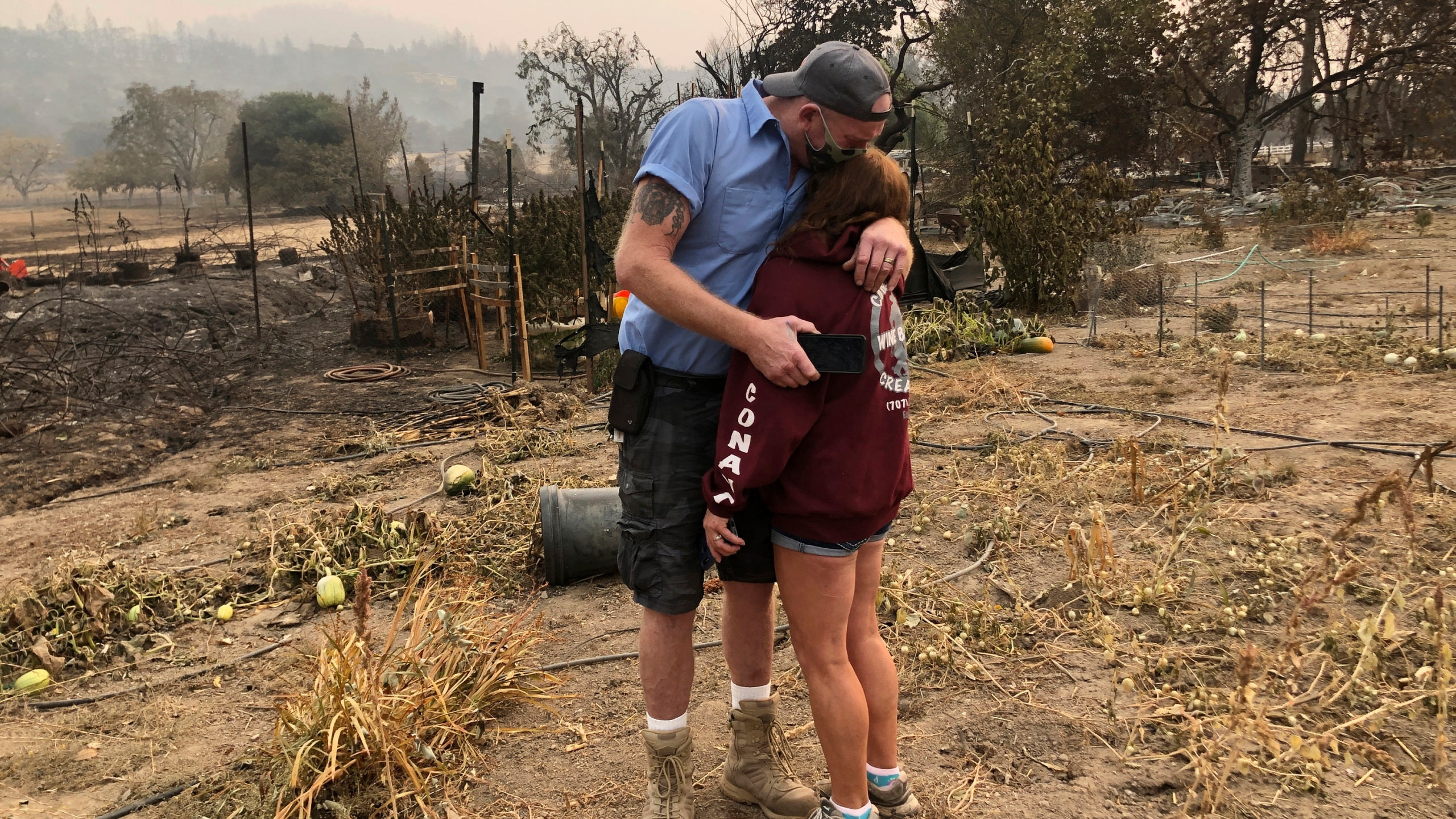 """Kevin Conant and his wife, Nikki, hug after looking at the debris of their burnt Santa Rosa home and business """"Conants Wine Barrel Creations"""" on Sept. 30, 2020, after the Glass/Shady fire completely engulfed it. (Haven Daley / Associated Press)"""