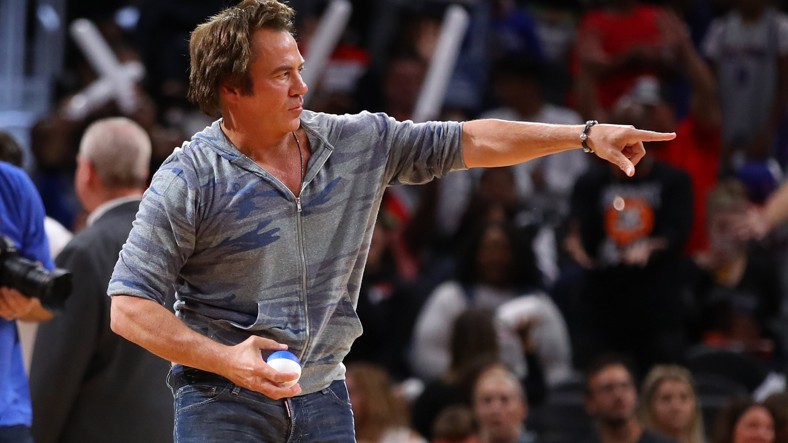 Owner of the Detroit Pistons Tom Gores throws a miniature basketball to fans during a pre-season game between the Orlando Magic and the Detroit Pistons at Little Caesars Arena in Detroit on Oct. 7, 2019. (Gregory Shamus / Getty Images)