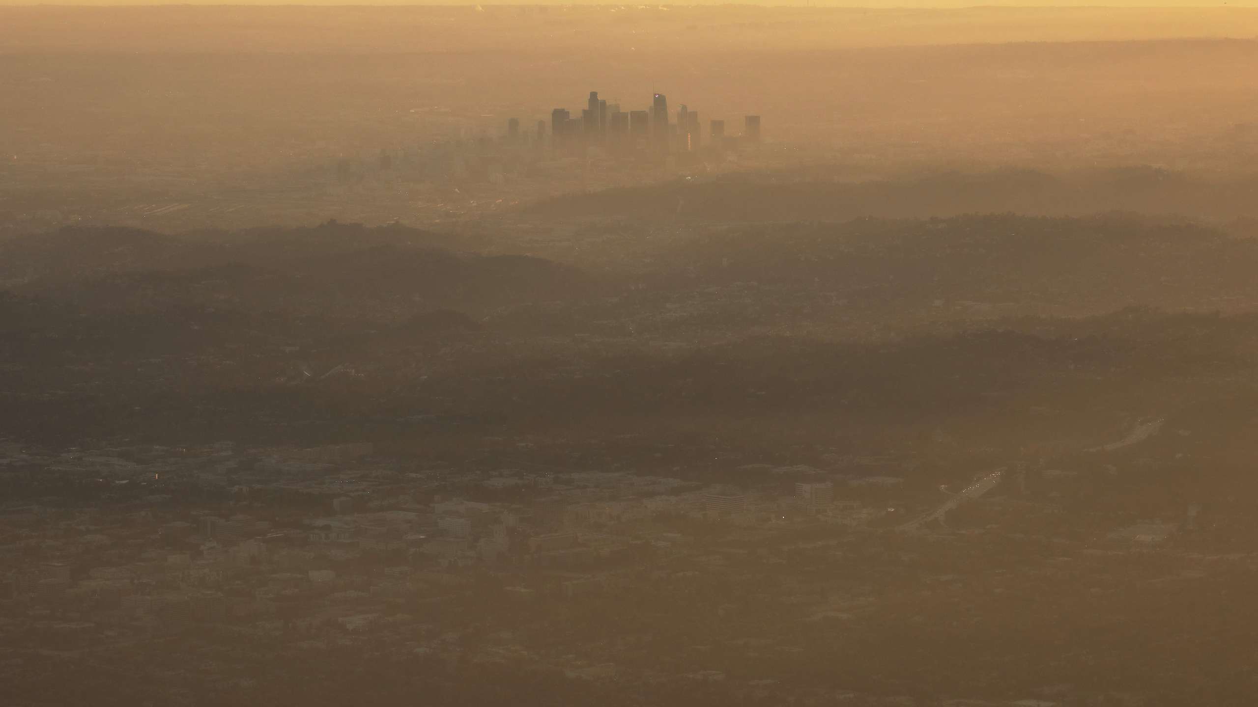 """The buildings of downtown Los Angeles are partially obscured in the late afternoon on Nov. 5, 2019 as seen from Pasadena. The air quality for metropolitan Los Angeles was predicted to be """"unhealthy for sensitive groups"""" that day by the South Coast Air Quality Management District. The Trump administration has begun officially withdrawing from the Paris Climate Agreement. A new report by more than 11,000 scientists worldwide states that the planet """"clearly and unequivocally faces a climate emergency."""" (Mario Tama/Getty Images)"""