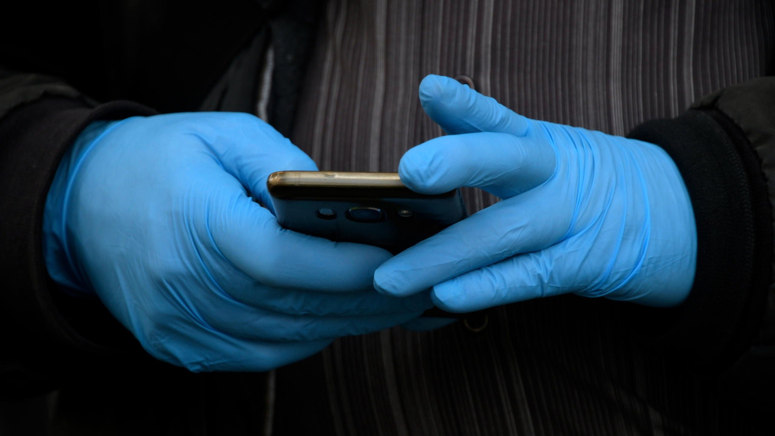 A man wearing gloves as a protective measure, holds a smartphone in Madrid on March 19, 2020. (GABRIEL BOUYS/AFP via Getty Images)