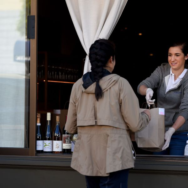 An employee for Atelier Crenn restaurant hands a takeout order to a customer through a window in San Francisco, Calif. on April, 1, 2020, during the novel coronavirus outbreak. (JOSH EDELSON/AFP via Getty Images)
