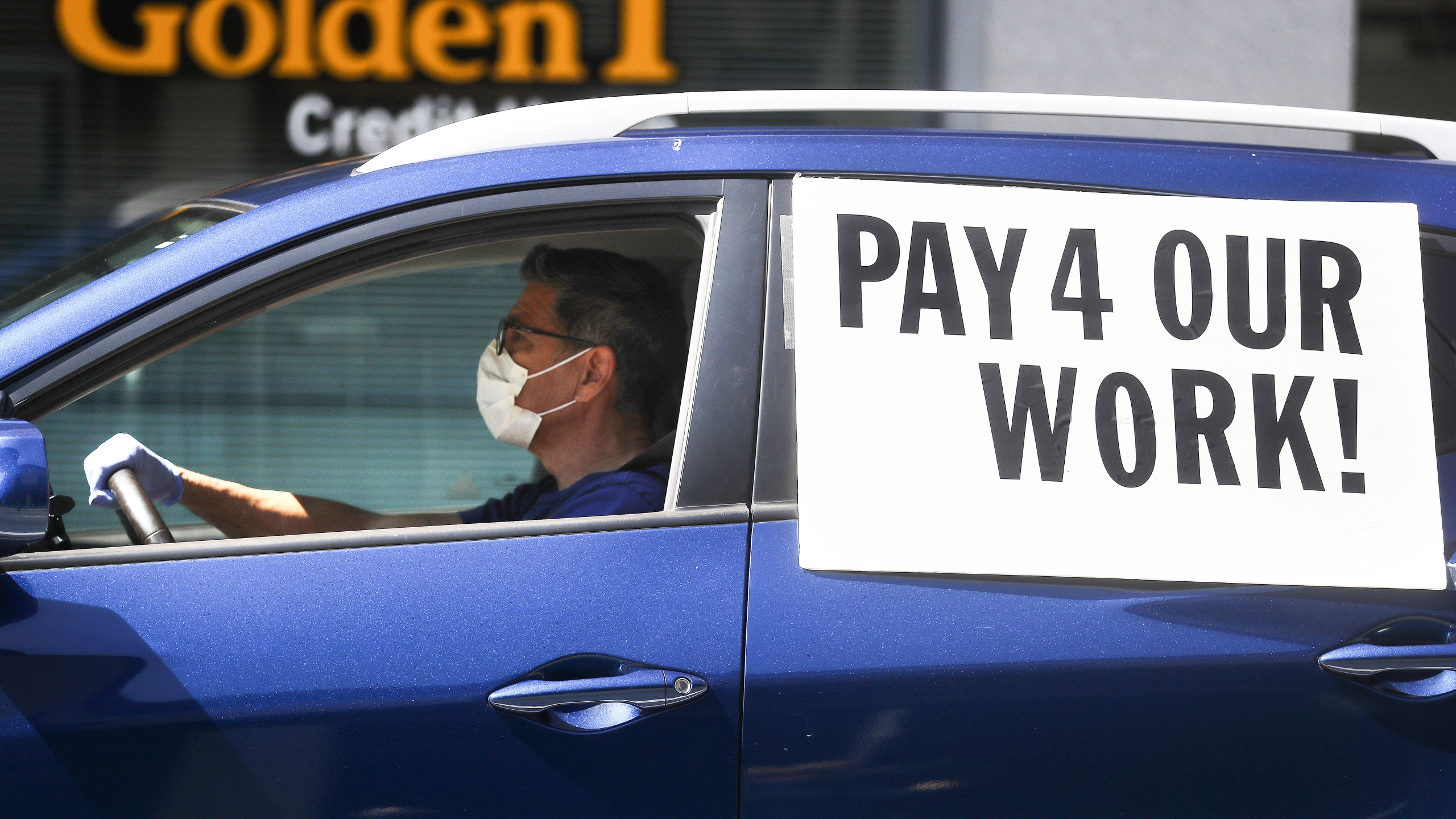 A driver wears a face mask and gloves as Uber and Lyft drivers protest outside the California Labor Commissioner's office, calling for California to enforce the AB 5 law on April 16, 2020 in Los Angeles. (Photo by Mario Tama/Getty Images)
