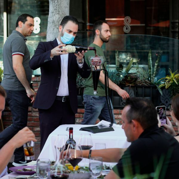 A waiter pours wine for patrons at an outdoor restaurant along 5th Avenue in The Gaslamp Quarter in downtown San Diego, California on July 17, 2020. (SANDY HUFFAKER/AFP via Getty Images)