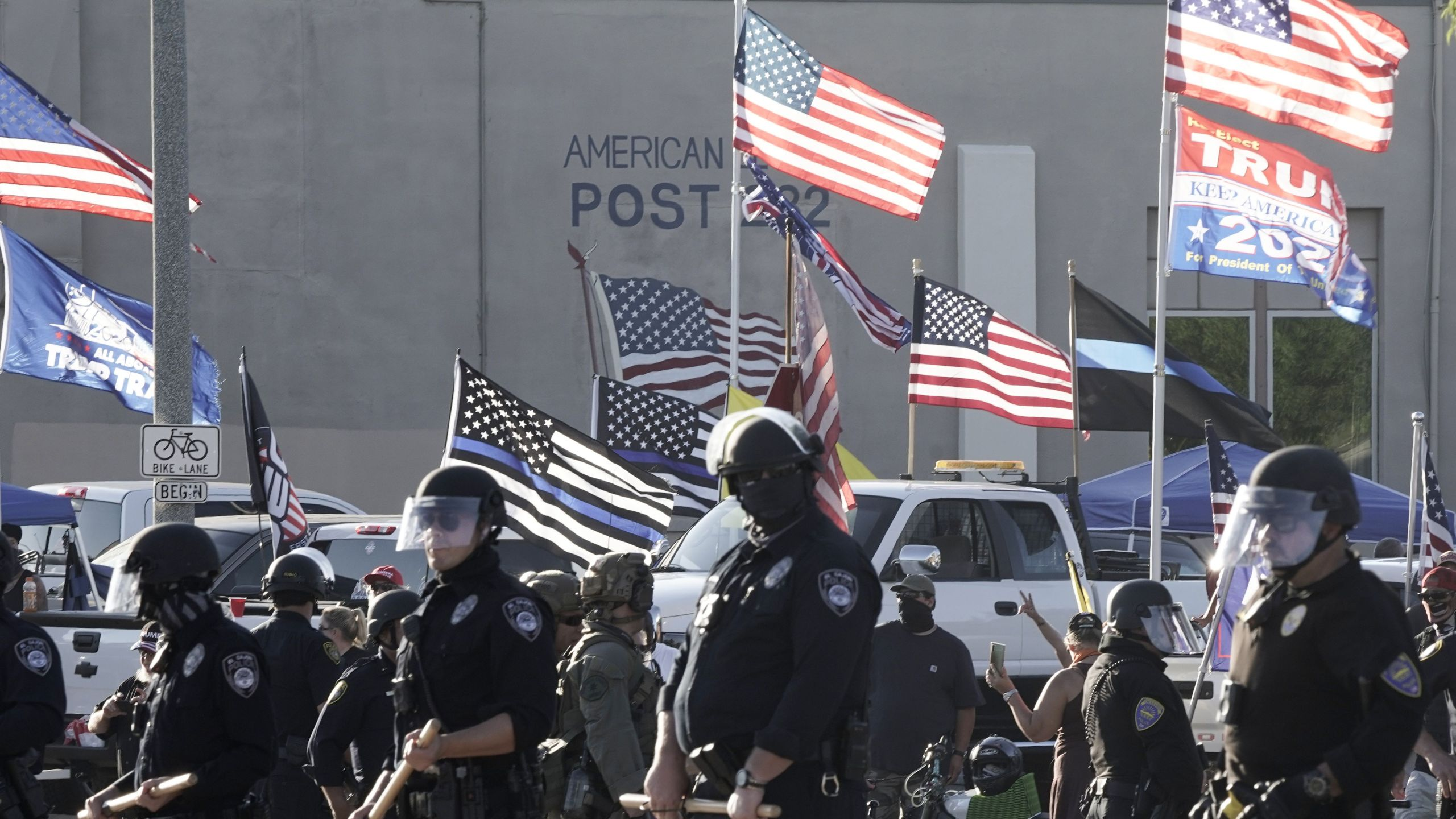 Officers of the El Cajon Police Department and San Diego Sheriff Department deputies separate right-wing counter-protestors at the American Legion Post 282 from Black Lives Matter demonstrators against racial injustice and police brutality in La Mesa, Calif. on Aug. 1, 2020. (Bing GUAN / AFP via Getty Images)