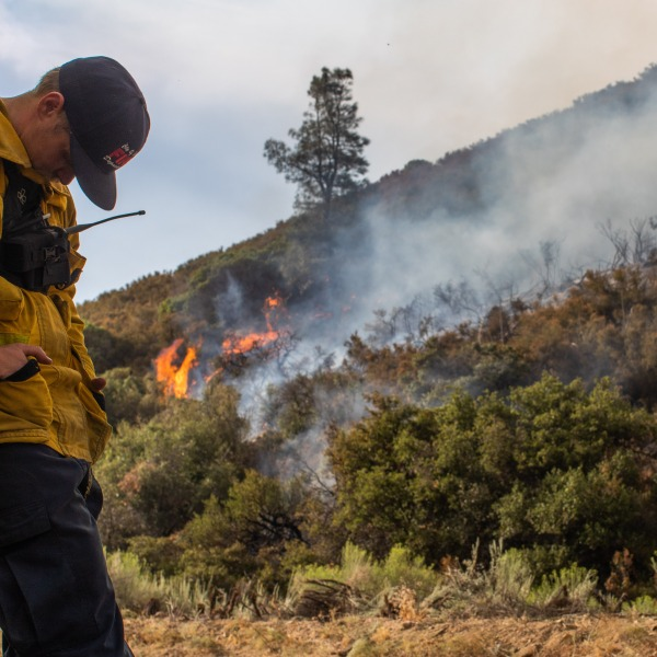 A Riverside firefighter takes a break from extinguishing hotspots from the Lake Fire at Pine Canyon Road in the Angeles National Forest, by Lake Hughes, 60 miles north of Los Angeles, California on Aug. 15, 2020. (APU GOMES/AFP via Getty Images)