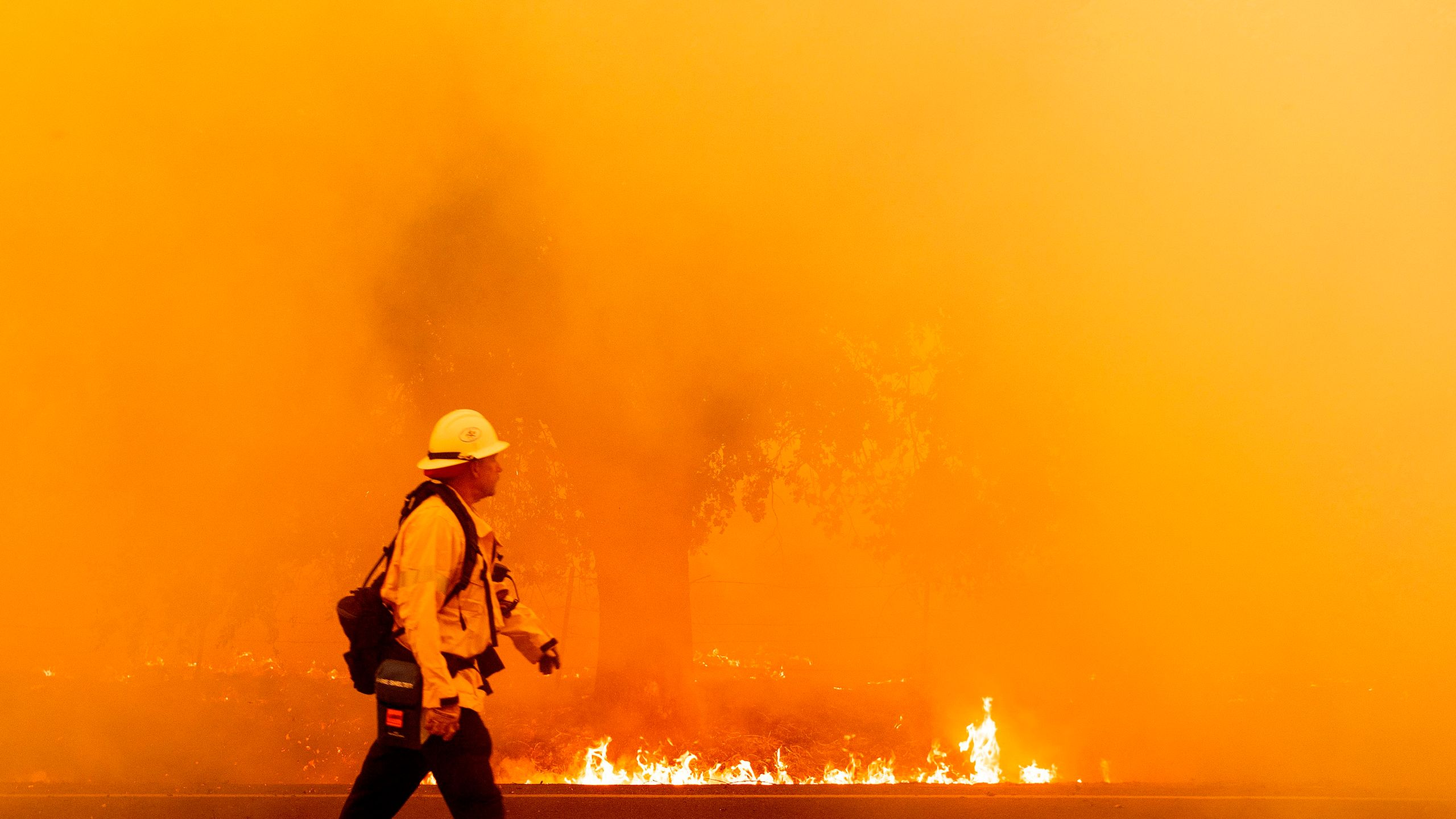 A Pacific Gas and Electric firefighter walks down a road as flames approach in Fairfield, Calif. during the LNU Lightning Complex fire on Aug. 19, 2020. (JOSH EDELSON/AFP via Getty Images)