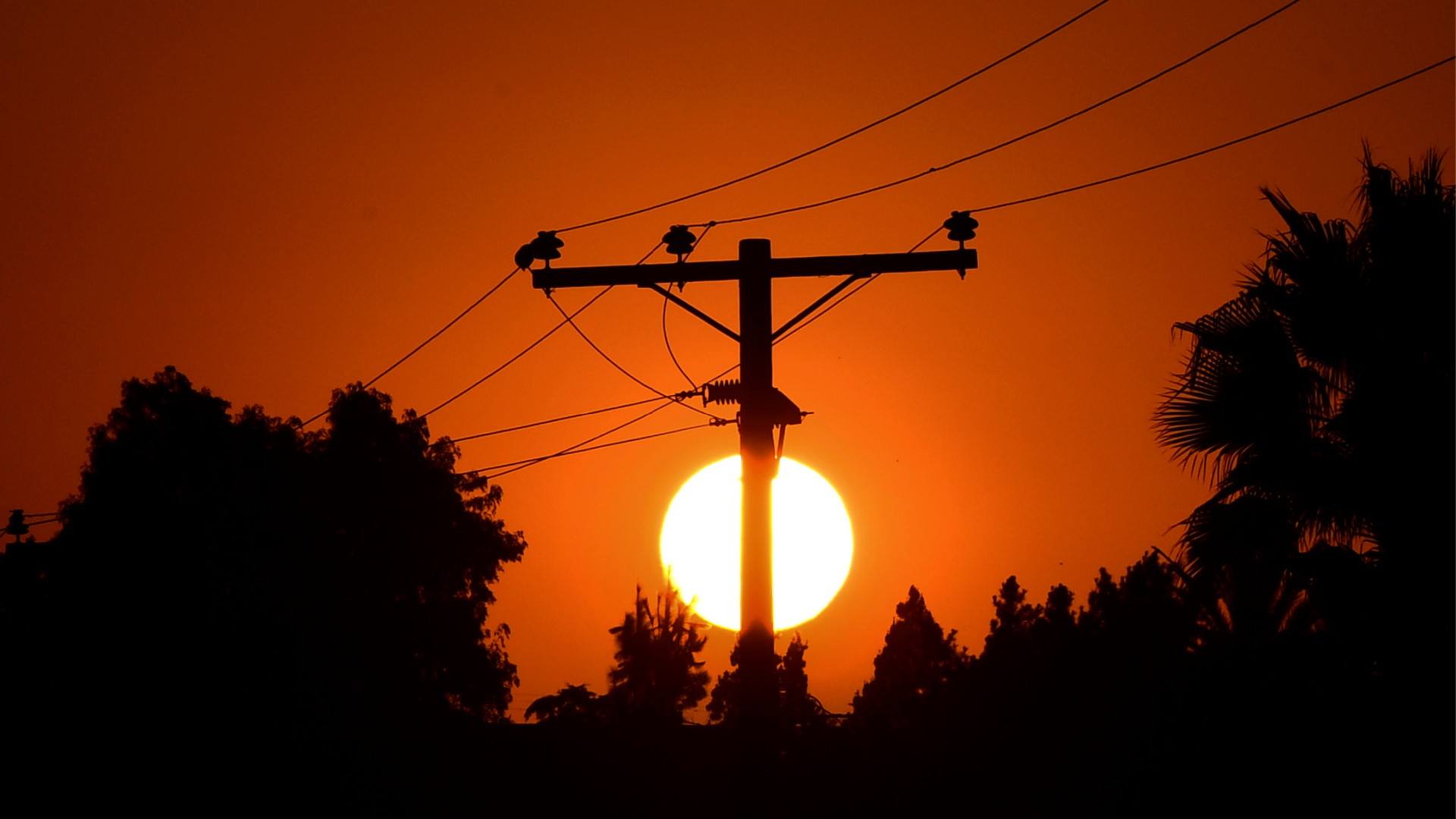 The sun sets behind power lines in Los Angeles on Sept. 3, 2020. (FREDERIC J. BROWN/AFP via Getty Images)