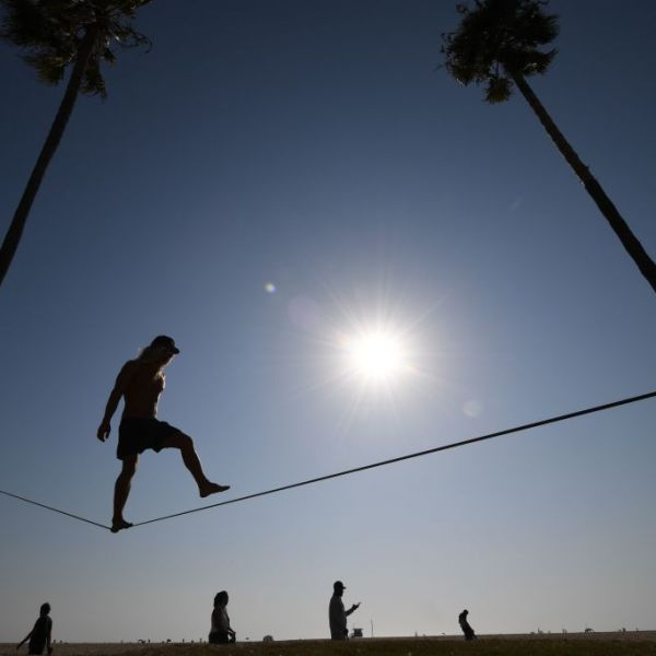 Chuck Reynolds practices his skill on a slack rope in Venice Beach where people flock to the ocean to escape the heat wave on Sept. 4, 2020. (ROBYN BECK/AFP via Getty Images)