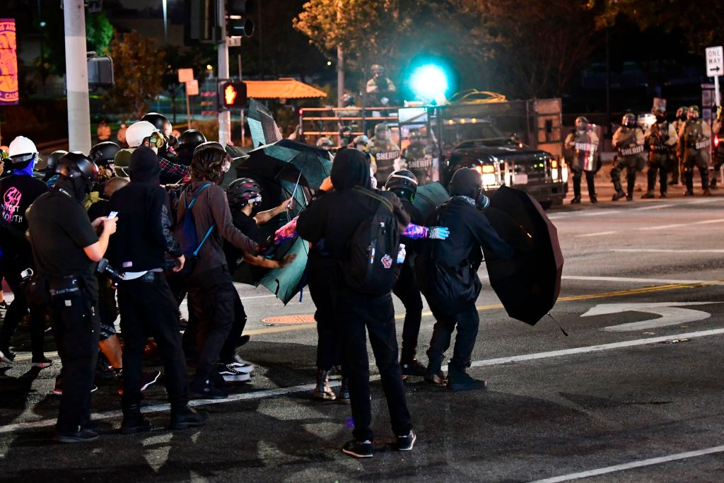 Protesters use umbrellas as shields from projectiles fired by Los Angeles County sheriff's deputies moving in to disperse a crowd of demonstrators gathered to protest again in the wake of Dijon Kizzee's killing, outside the South L.A. sheriff's station on Sept. 8, 2020 in Los Angeles, California. (FREDERIC J. BROWN/AFP via Getty Images)