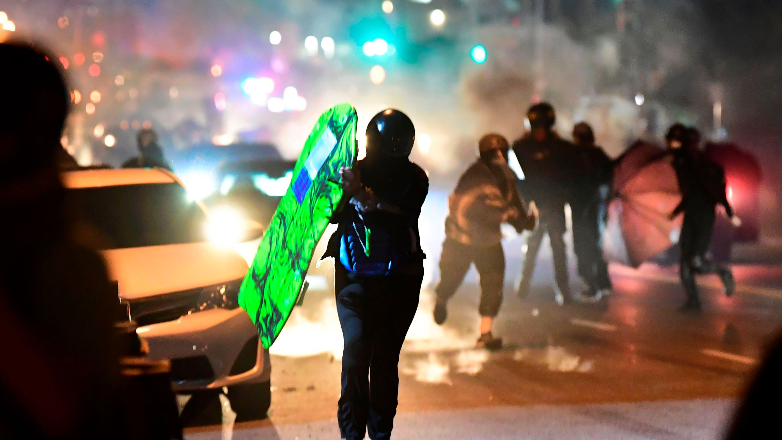 People run from tear gas and rubber bullets fired by Los Angeles County sheriff's deputies dispersing a crowd of demonstrators gathered to protest again in the wake of Dijon Kizzee's killing, outside the South LA sheriff's station on Sept. 8, 2020. (FREDERIC J. BROWN/AFP via Getty Images)