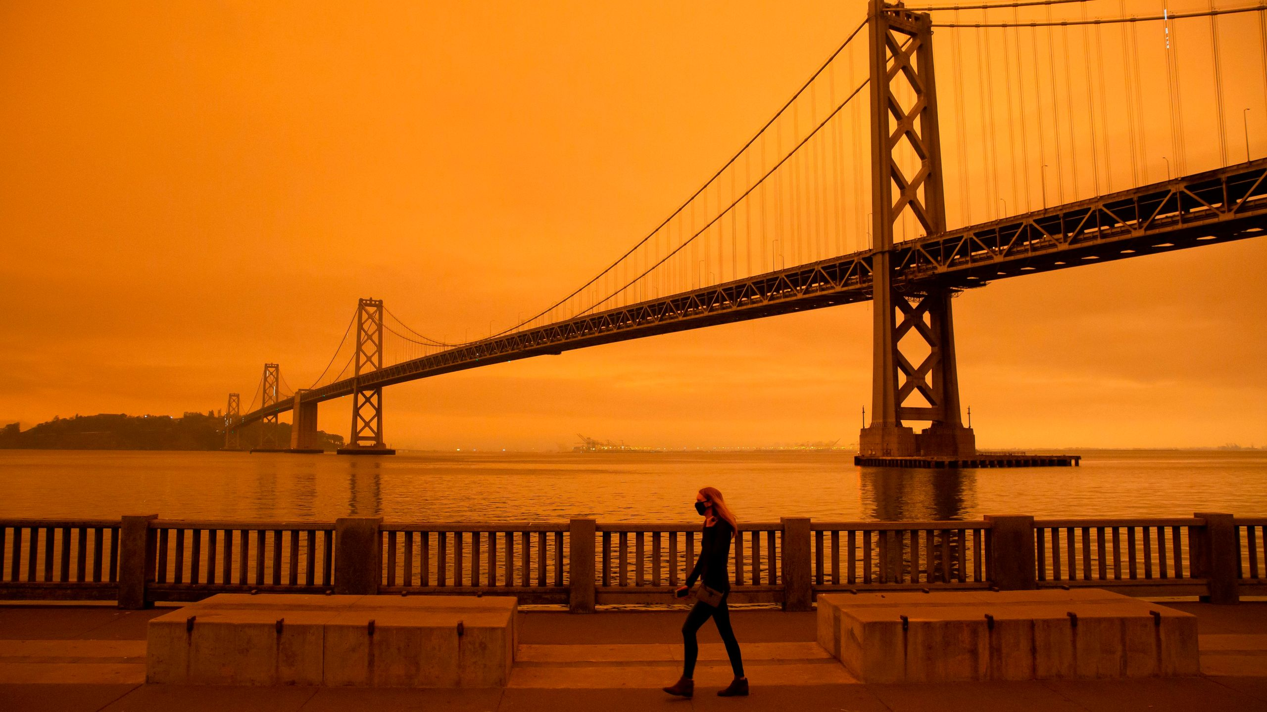 A woman walks along The Embarcadero under an orange smoke-filled sky in San Francisco on Sept. 9, 2020. (Brittany Hosea-Small / AFP / Getty Images)