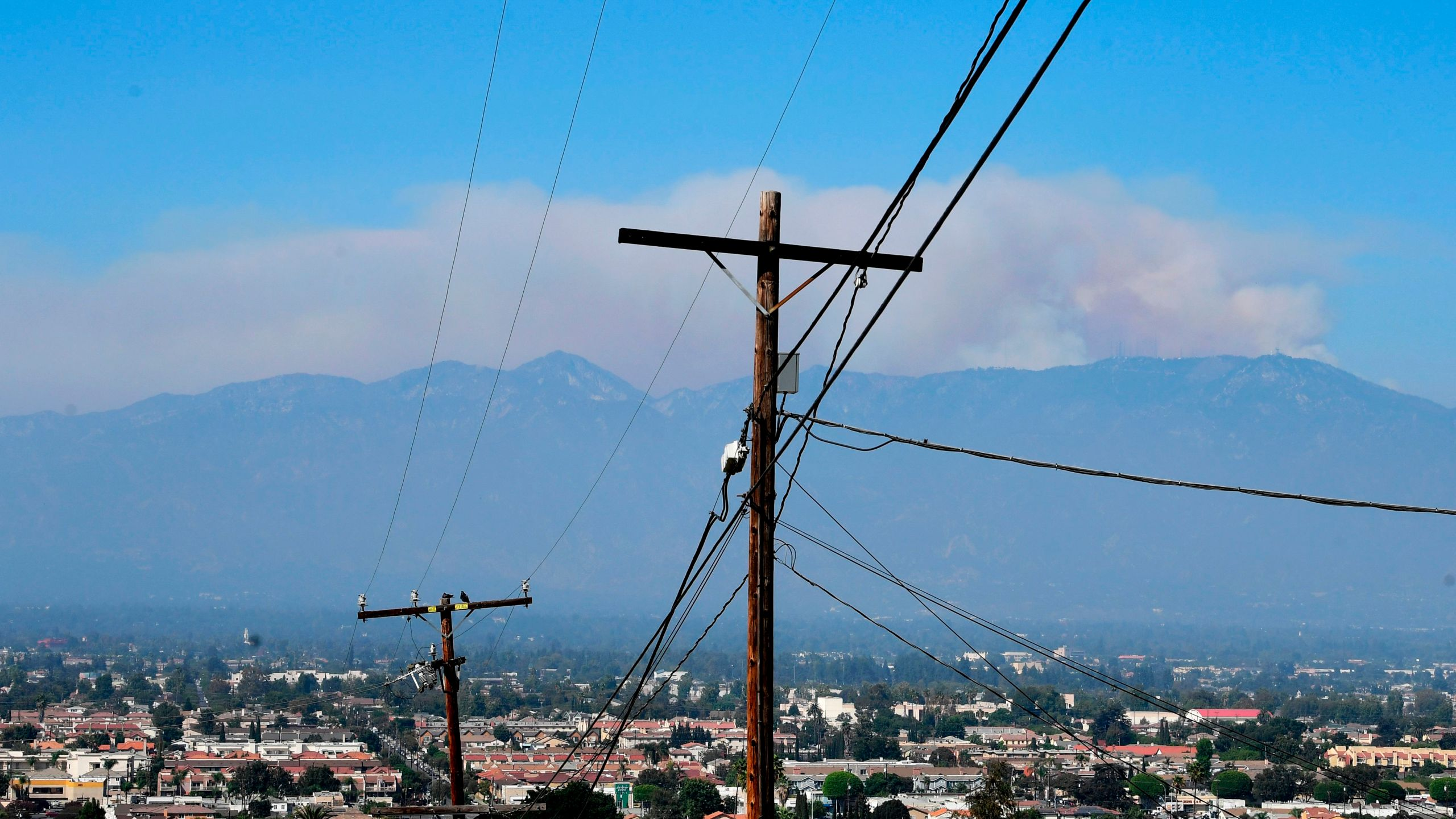 A huge plume of smoke from the Bobcat Fire rises from the Angeles National Forest over the San Gabriel Mountains as seen from Monterey Park, California on September 21, 2020. (FREDERIC J. BROWN/AFP via Getty Images)