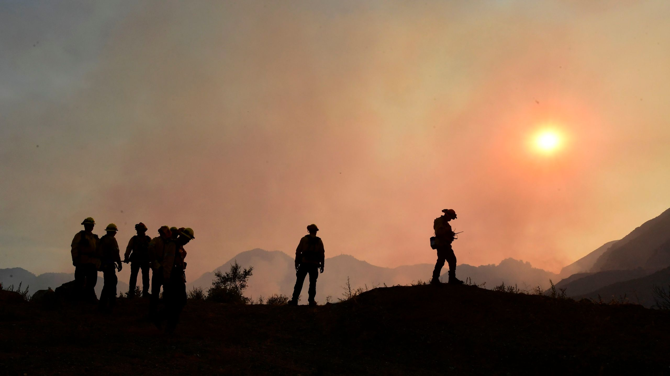 Firefighters position themselves on a ridge overlooking smouldering fires from the Bobcat Fire in a valley below in the Angeles National Forest on Sept. 23, 2020 in Los Angeles. (FREDERIC J. BROWN/AFP via Getty Images)