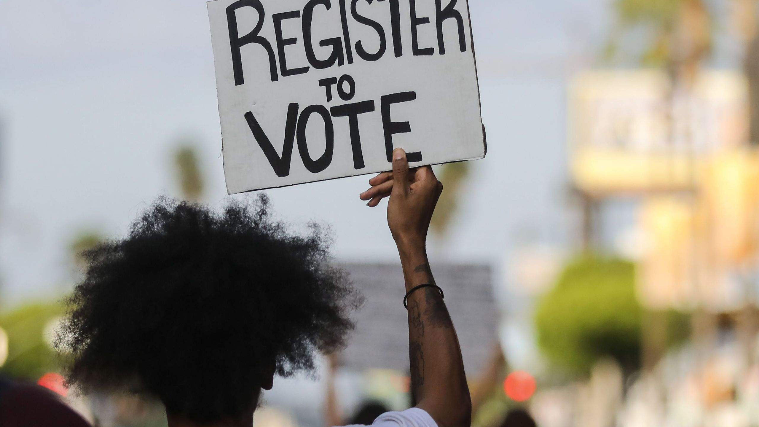 """A man carries a """"register to vote"""" sign during a demonstration on June 6, 2020 in Los Angeles. (Mario Tama/Getty Images)"""