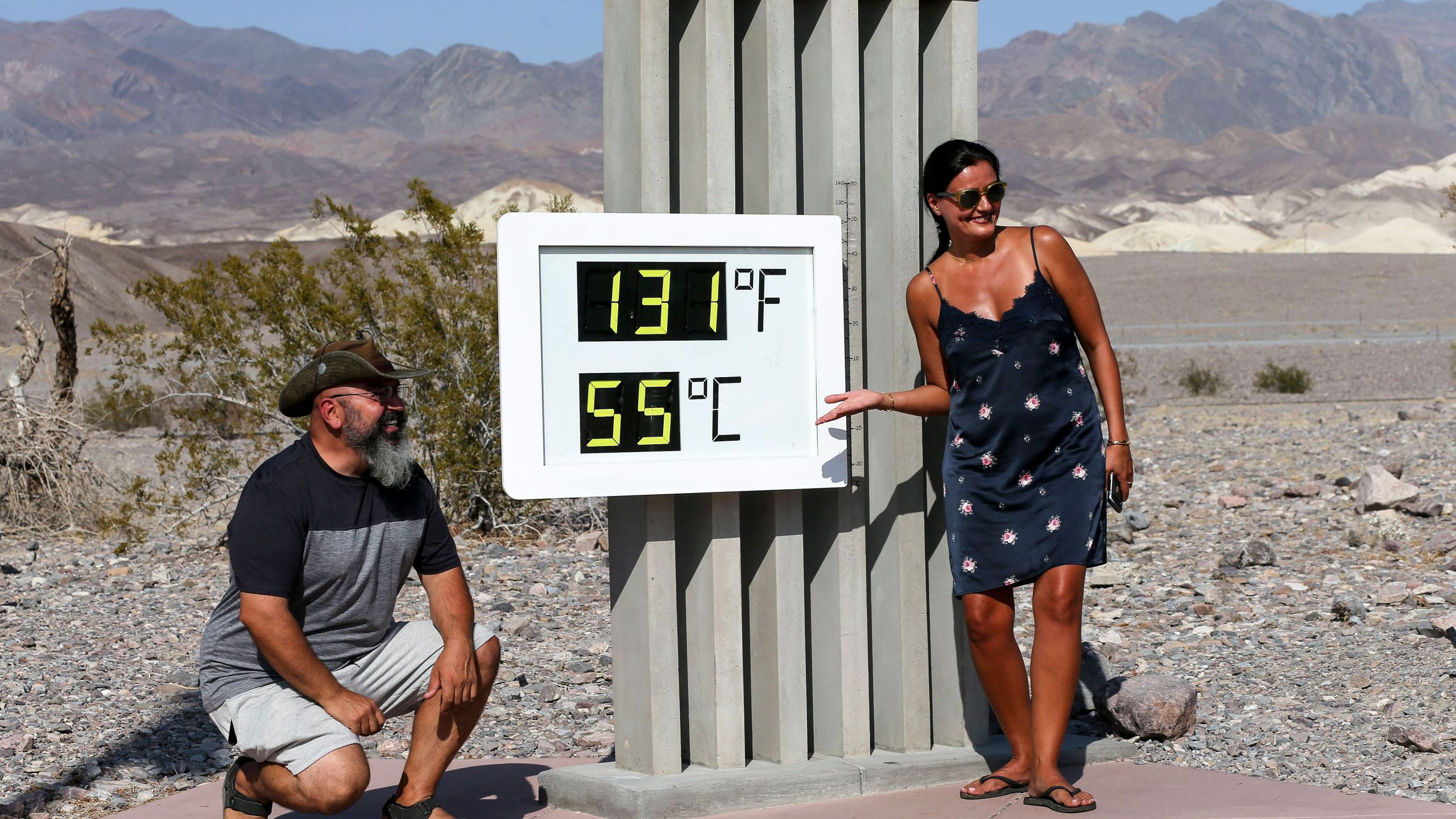 Visitors gather for a photo in front of an unofficial thermometer at Furnace Creek Visitor Center on August 17, 2020 in Death Valley National Park. (Mario Tama/Getty Images)