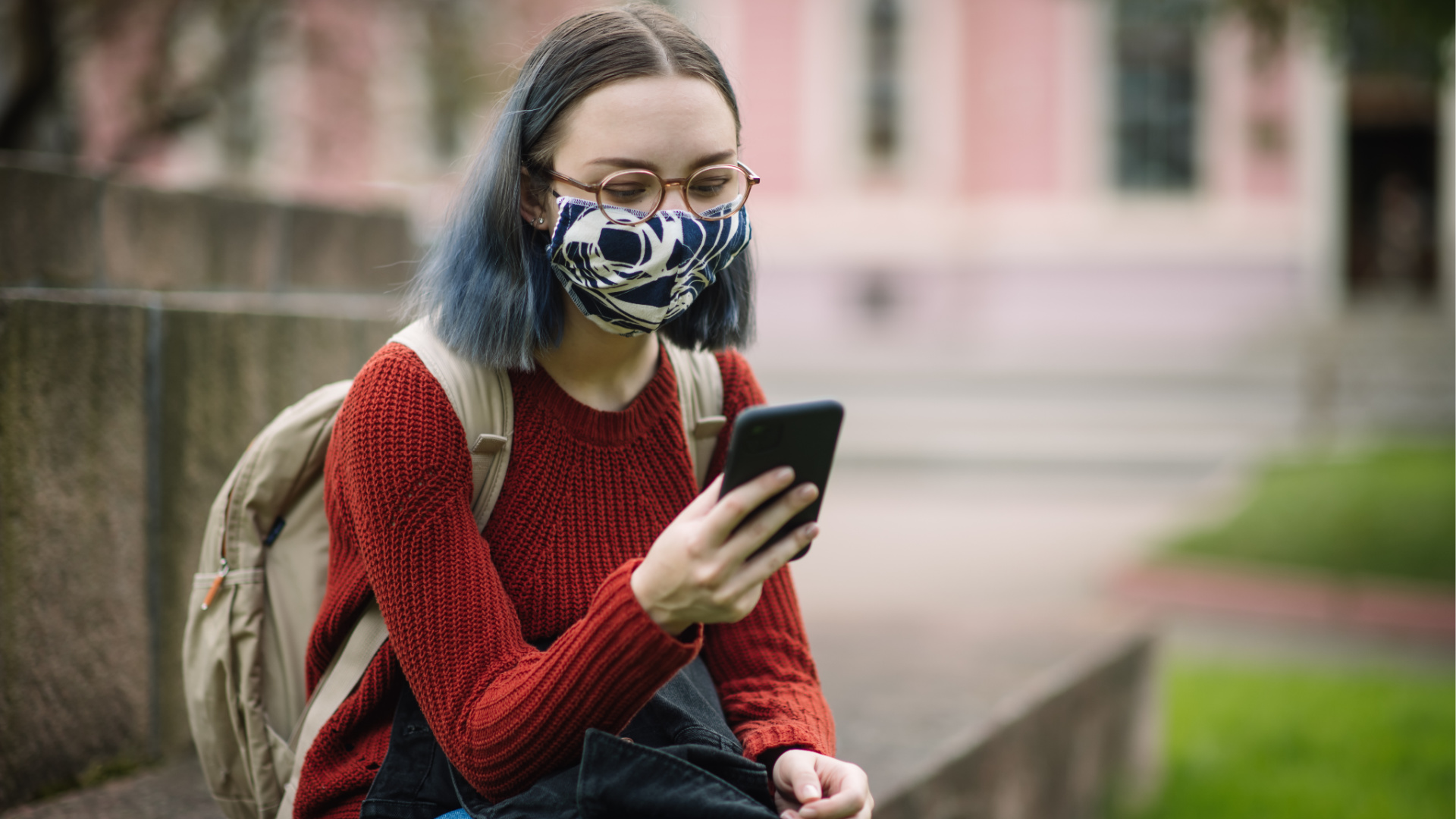 A student in a face mask checks her phone in this undated file photo. (Getty Images)
