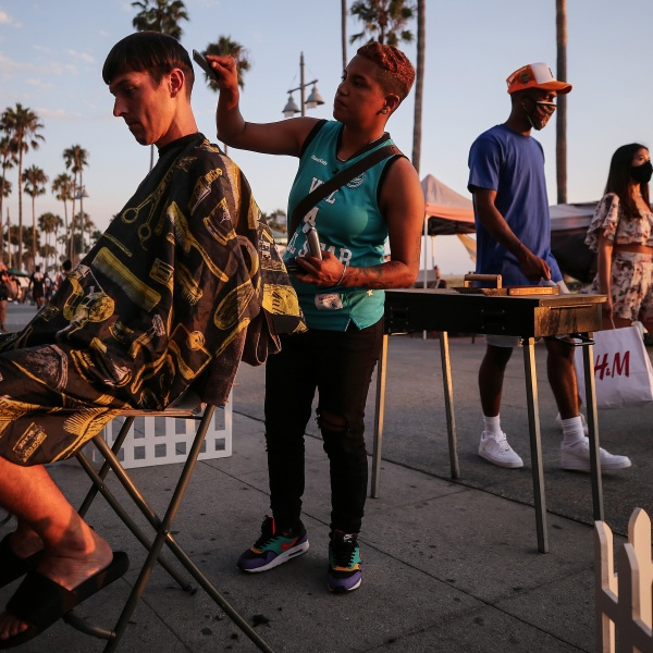 Joy Aguilar cuts Cooper Vanhoose's hair on the Venice Beach boardwalk on the first day of the Labor Day weekend amid a heatwave on Sept. 5, 2020 in Venice, Calif. Aguilar said she is offering haircuts outdoors along the beach as many hair salons remain closed due to the coronavirus pandemic. Temperatures soared across California that day. (Mario Tama/Getty Images)