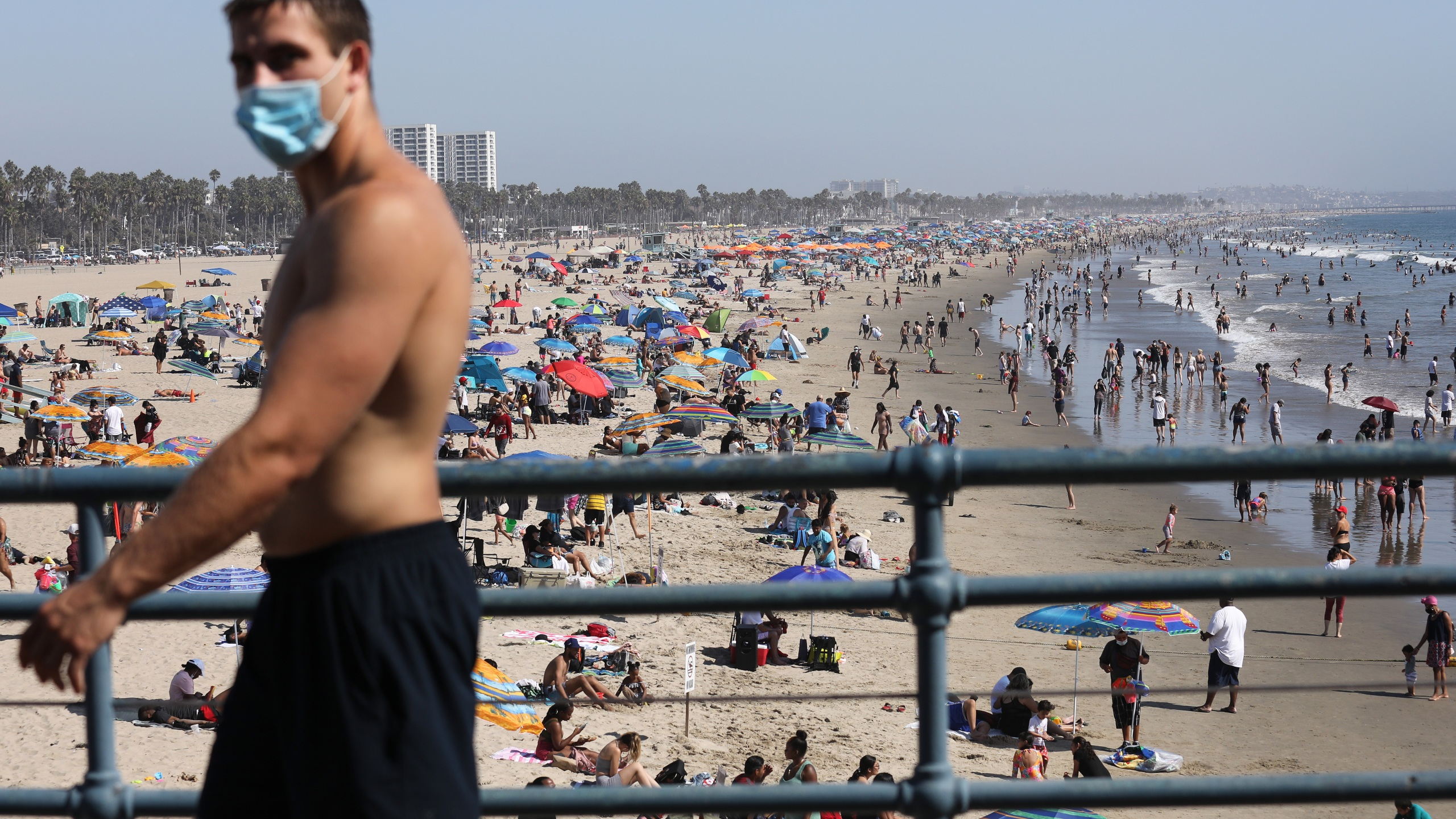 A man wears a face covering at the pier on the first day of the Labor Day weekend amid a heatwave on Sept. 5, 2020 in Santa Monica. (Photo by Mario Tama/Getty Images)