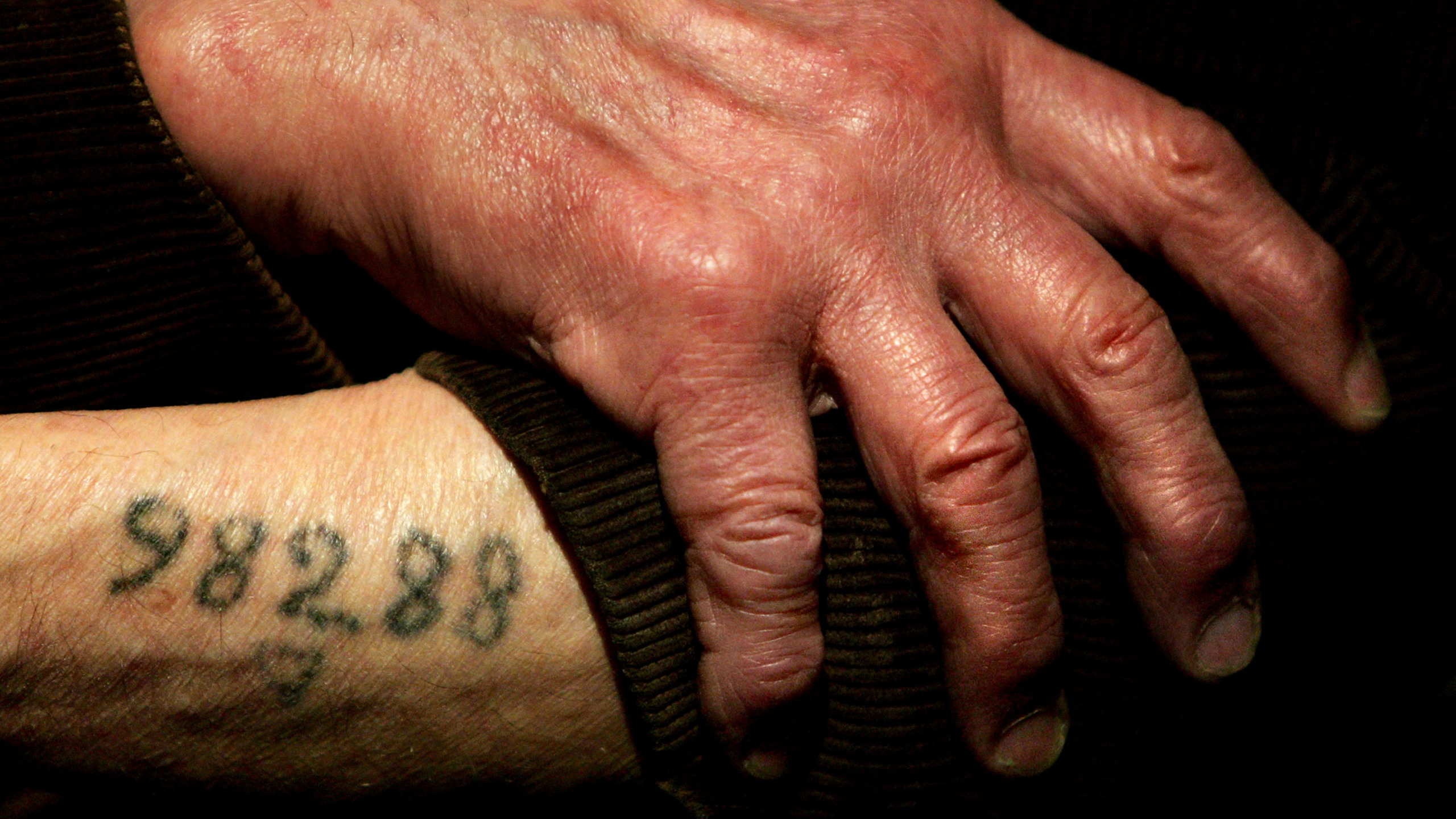 Auschwitz survivor Leon Greenman, prison number 98288, displays his number tattoo on Dec. 9, 2004, at the Jewish Museum in London. (Ian Waldie / Getty Images)