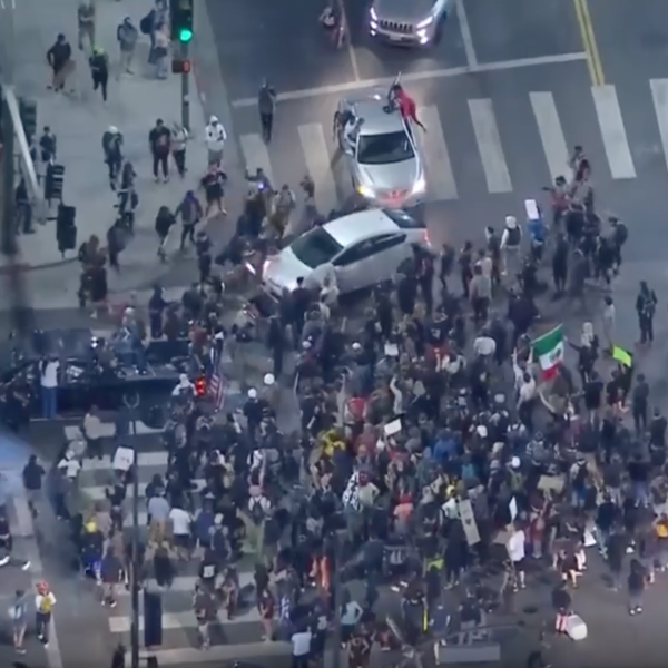 A Prius drives through a crowd of protesters in Hollywood on Sept. 24, 2020. (KTLA)