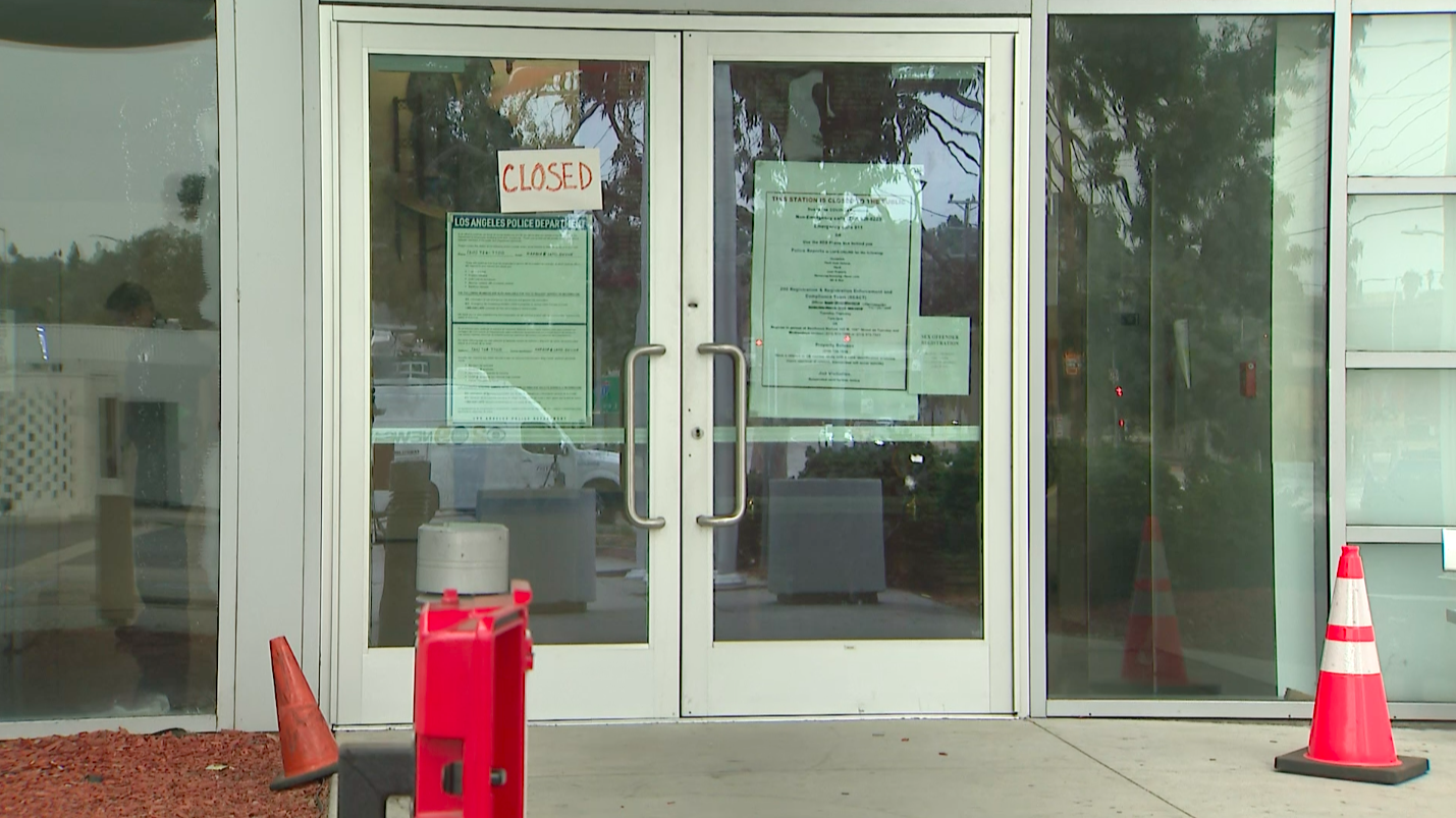 "A ""closed"" sign is taped to the door at LAPD's Harbor Division station in San Pedro on Sept. 27, 2020. (KTLA)"