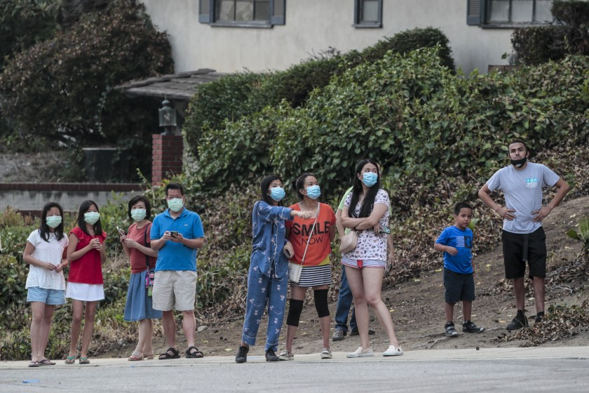 Onlookers gather Sunday at Highland Oaks Drive And Elkins Avenue in Arcadia to check the progress of the Bobcat fire as it creeps ever closer from the nearby Angeles National Forest.(Robert Gauthier / Los Angeles Times)