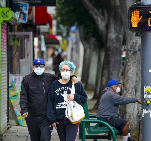 Two people in face masks walk down Cesar E. Chavez Boulevard near downtown Los Angeles in this undated photo.(Irfan Khan / Los Angeles Times)