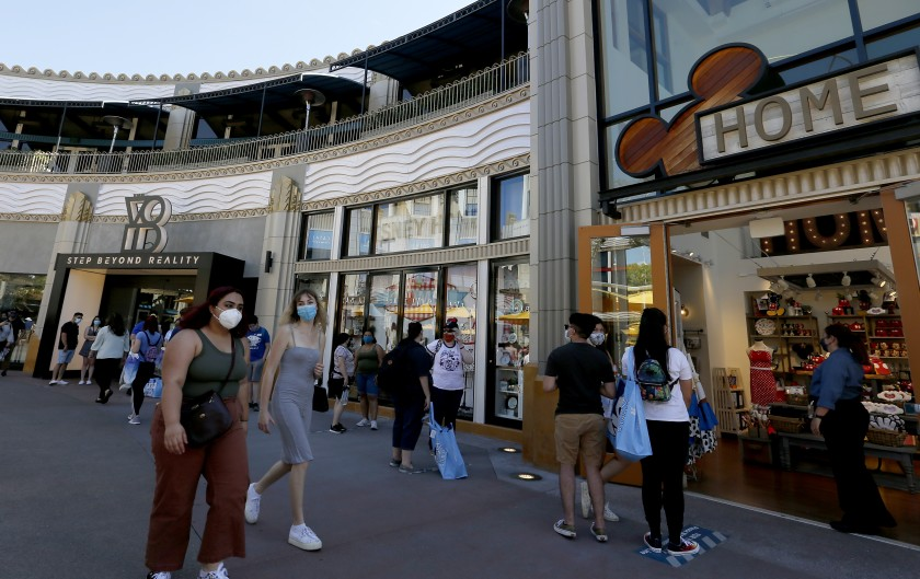 People stroll through the Downtown Disney shopping district in Anaheim in July. (Luis Sinco / Los Angeles Times)