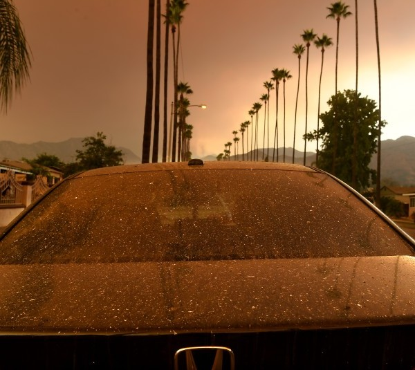 Ash falls on a parked car as the Bobcat Fire burns in the distance Wednesday morning. (Wally Skalij / Los Angeles Times)