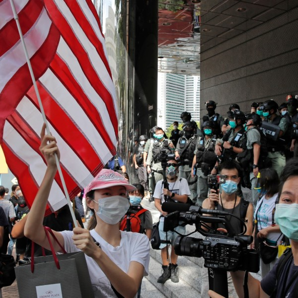 In this July 4, 2020, file photo, a woman carries an American flag during a protest outside the U.S. Consulate in Hong Kong. (AP Photo/Kin Cheung, File)