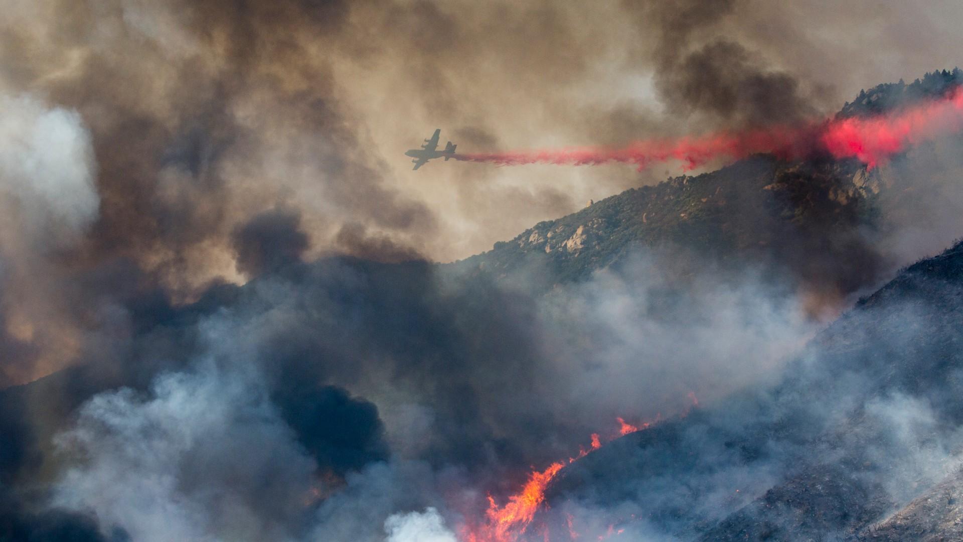 In this Saturday, Sept. 5, 2020 file photo, an air tanker drops fire retardant on a hillside wildfire in Yucaipa, Calif. (AP Photo/Ringo H.W. Chiu)