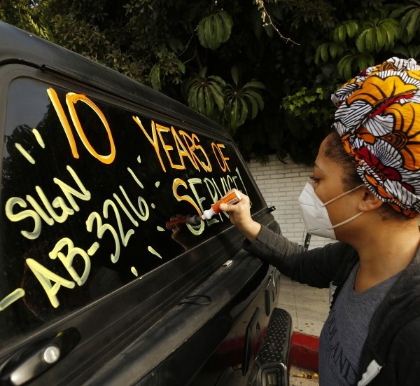 Courtney Banks who has worked in events and catering at the Chateau Marmont writes message on windows of vehicles in support of workers who lost their jobs at the hotel in this undated photo.(Al Seib/Los Angeles Times)