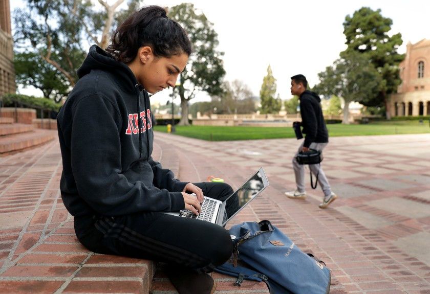 Student Shaya Naimi, 19, hangs out on the steps of the Powell Library at UCLA, where classes moved to online only in March. (Christina House / Los Angeles Times)