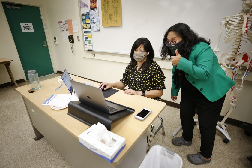 Eagle Rock Junior/Senior High School Principal Mylene Keipp, right, interacts virtually with students alongside teacher Arlene Alpuerto in August. The hiring of teachers boosted government-sector payrolls.(Al Seib / Los Angeles Times)