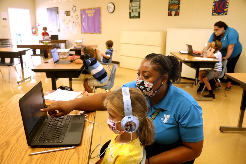 Denecia Boone, a teacher with the YMCA, helps Maya Haldeman, foreground, with an exercise at the Anza Elementary School campus in Torrance. (Genaro Molina / Los Angeles Times)
