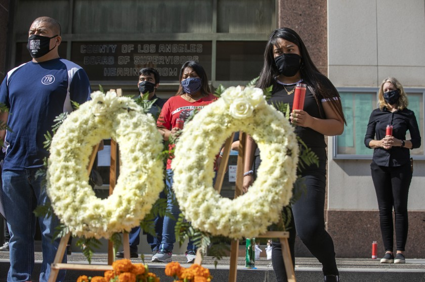 Overhill Farms workers take part in an Aug. 31 memorial ceremony in front of the Kenneth Hahn Hall of Administration in downtown Los Angeles to honor those who have died of COVID-19.(Mel Melcon / Los Angeles Times)