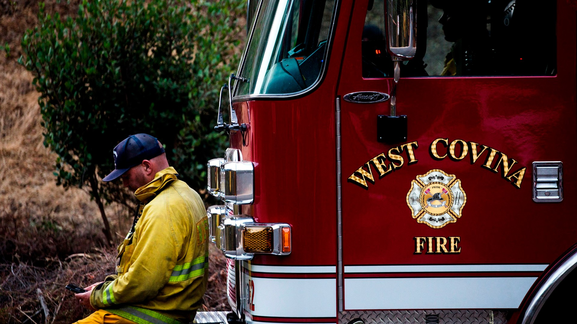West Covina firefighters rest on their fire truck as the Bobcat Fire burns in the San Gabriel mountains above Monrovia on September 16, 2020. (RINGO CHIU/AFP via Getty Images)