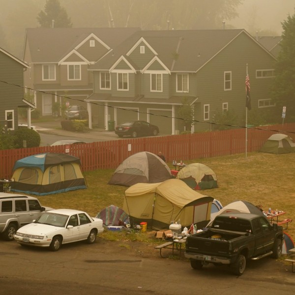 Evacuees from the Riverside Fire stay in tents at the Milwaukie-Portland Elks Lodge, Sunday, Sept. 13, 2020, in Oak Grove, Ore. (AP Photo/John Locher)
