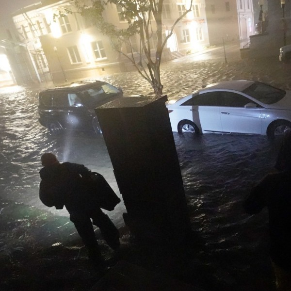 People use flashlights as they walk on flooded streets in search of their vehicle, Wednesday, Sept. 16, 2020, in Pensacola, Fla. (AP Photo/Gerald Herbert)
