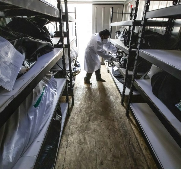 Manuel Aguilar, a driver for Continental Funeral Home in East Los Angeles, tends to bodies of COVID-19 victims stored in a refrigerated truck in this undated photo.(Robert Gauthier / Los Angeles Times)