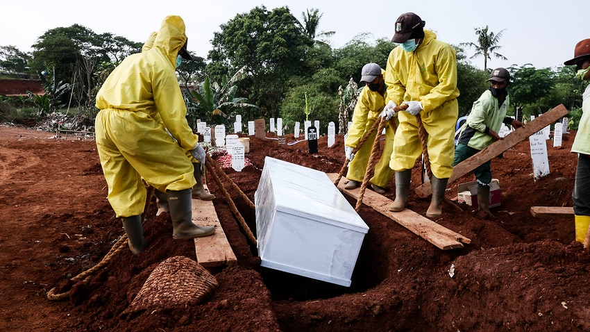 Funeral workers wearing protective suits bury a coffin of a coronavirus victim at Pondok Ranggon cemetery in Jakarta, Indonesia on Sept. 9, 2020. The cemetery of Pondok Ranggon is almost full as Jakarta's administration recorded more than 5,000 bodies buried with COVID-19 protocols. (Photo by Anton Raharjo/Anadolu Agency via Getty Images)