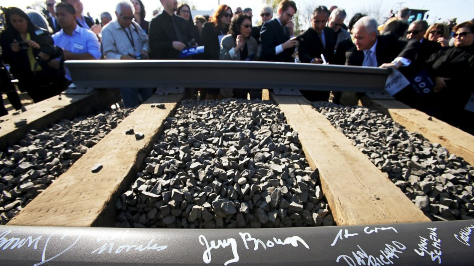 Guests, including then Gov. Jerry Brown, sign a rail segment during a groundbreaking ceremony for a California bullet train station in Fresno on Jan. 6, 2015.(Los Angeles Times)
