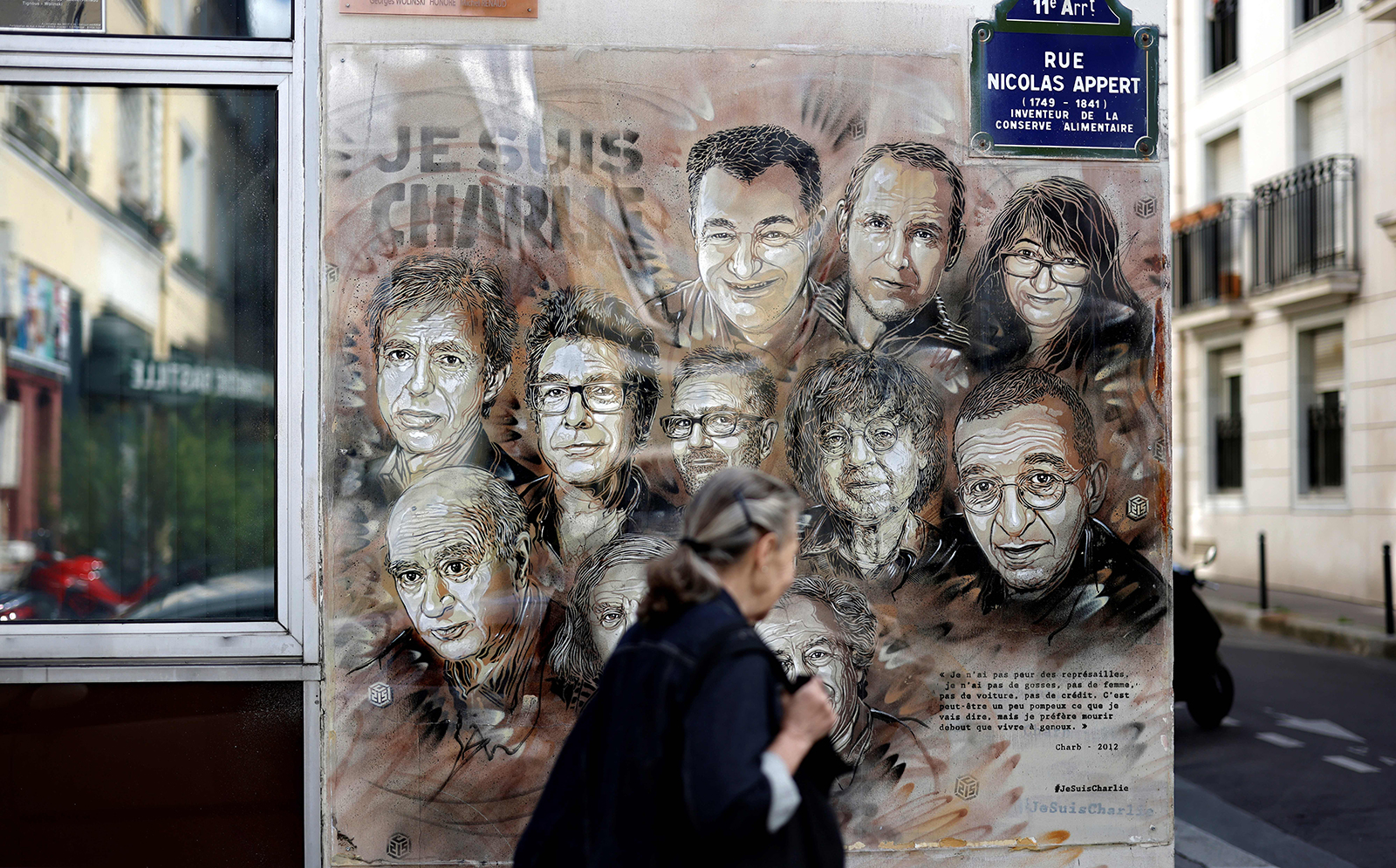 A woman walks past a painting on August 31 in tribute to those killed in the Charlie Hebdo attack by jihadist gunmen in January 2015, in Paris. (Thomas Coex/AFP/Getty Images via CNN Wire)