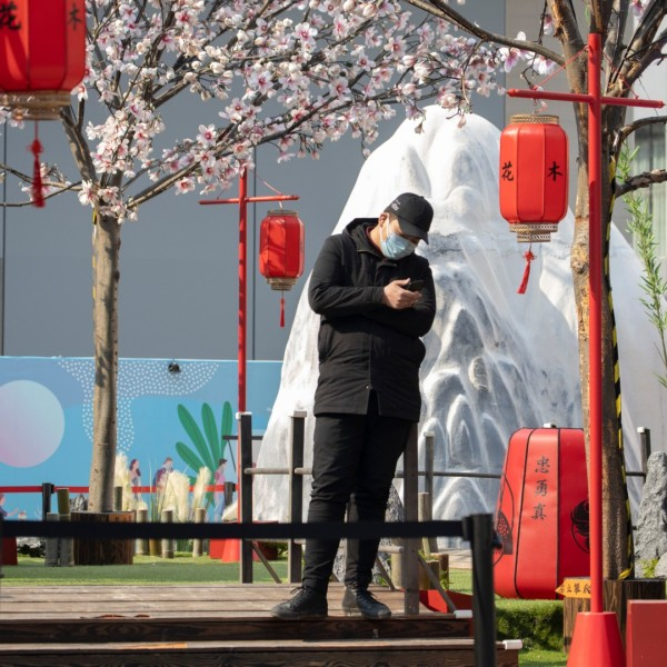 """A man stands in a set promoting the Disney movie """"Mulan"""" in Beijing on Wednesday, Feb. 19, 2020. (AP Photo/Ng Han Guan)"""